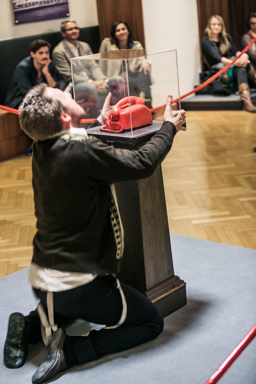 Museumswärter vor einem roten Telefon