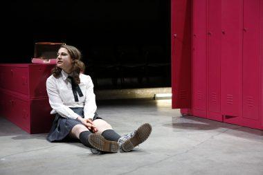 Katie sitzt am Boden, an Spind gelehnt