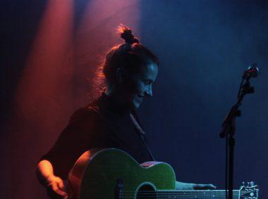 Maike Rosa Vogel ist mit einer Gitarre in dunklem Licht zu sehen, sie trägt ihre Haare hochgebunden und lächelt.